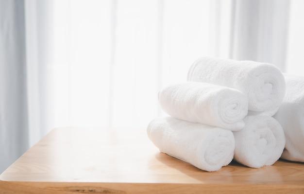 Чистые белые полотенца сложены на деревянном столе с размытым белым фоном ванной