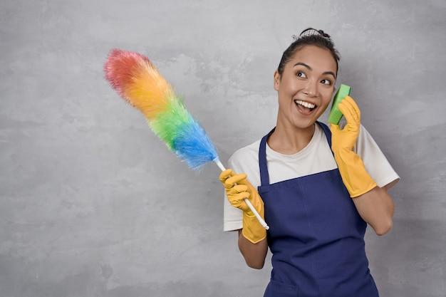 カラフルなマイクロファイバーダスターとキッチンスポンジを保持している制服を着た楽しい遊び心のある若い女性できれい