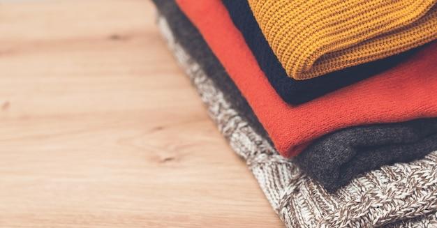 スタックのきれいなウールの服、上面図。木製の背景にニットの暖かい服のスタック。ニットカラーの洋服、ヴィンテージスタイル。テーブルの上のセーターの山。秋冬シーズンのニットウェア。
