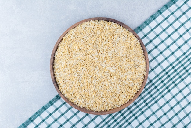 Очищенный и сушеный коричневый рис на большом деревянном подносе на выложенной скатерти на мраморной поверхности.