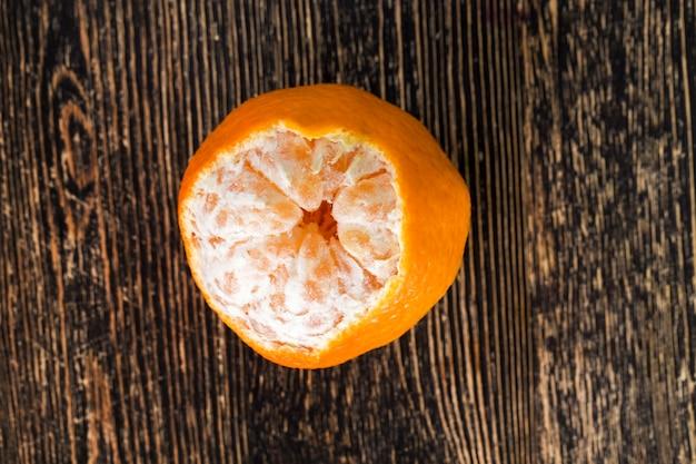 皮からきれいにされたおいしいオレンジは食べる準備ができています、ピースはテーブルの上に横たわっています