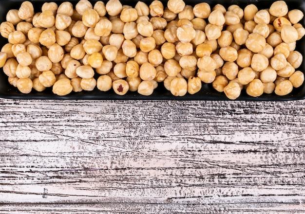 Nocciole pulite in un piatto a forma di rettangolo su un tavolo di legno bianco. avvicinamento.