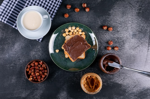 Cleaned and shelled hazelnuts in a green glassy plate with cocoa spread bread, milk flat lay on a dark stone table