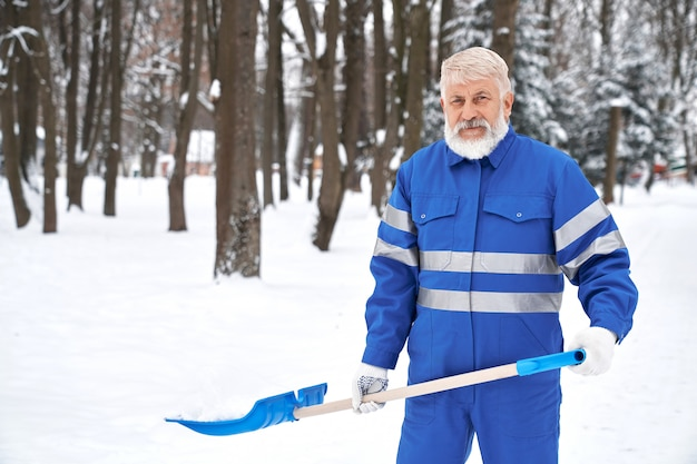 Очиститель в синем рабочем комбинезоне с защитной лентой.