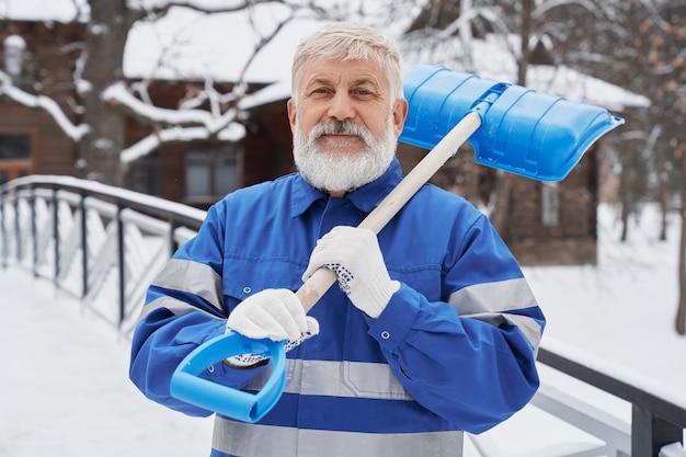 Уборщик в рабочей спецодежде с лопатой на зимнем дворе.