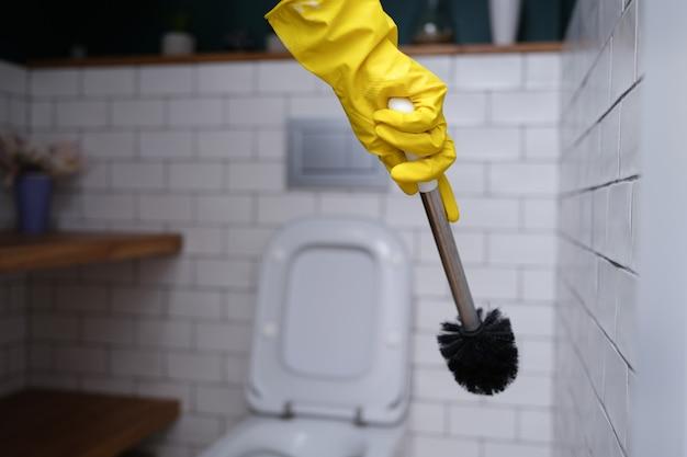 トイレブラシのクローズアップを保持している黄色のゴム手袋のクリーナー