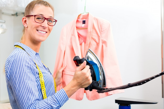 Cleaner in laundry shop ironing jacket