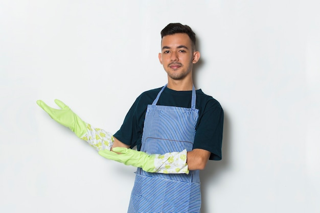 Cleaner man wearing apron and gloves pointing with hand and finger up to the side