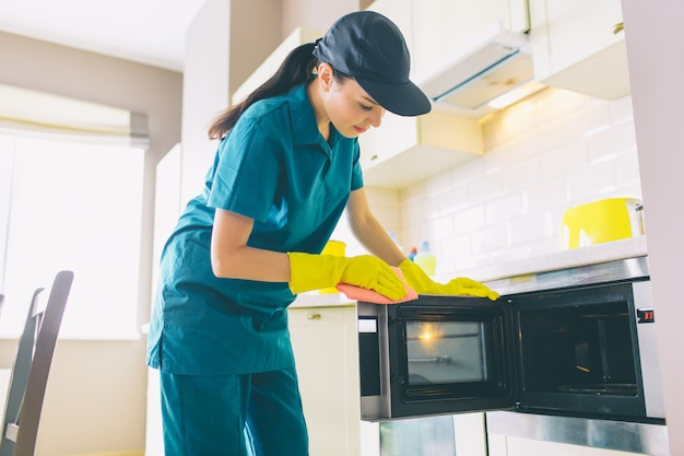 Cleaner stands in kitchen and cleans surface of microvawe owen
