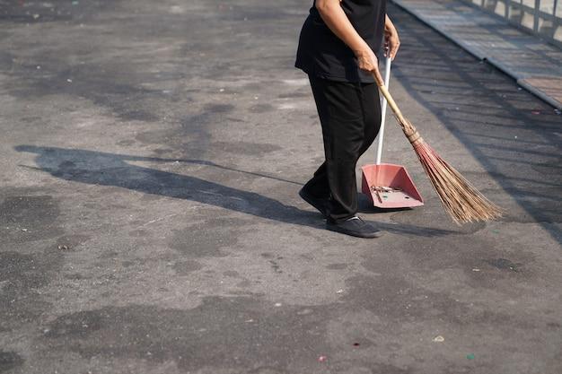 Cleaner sweep trash in large asphalt outdoor area at noon.