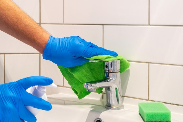 The cleaner washes the sink faucet in bathroom with detergents. cleaning to create hygiene and purity