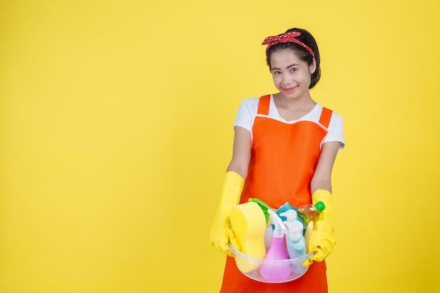 Уборка красивая женщина с прибором чистки на желтом цвете.