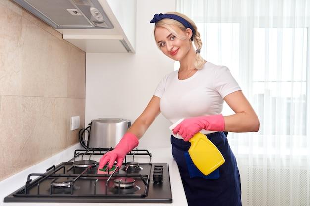 Очистка газовой плиты кухонной утварью, бытовые концепции или гигиена и уборка.