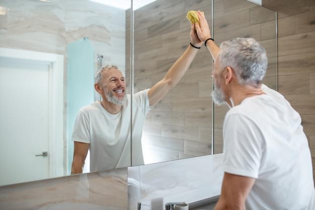 クリーニング。いくつかの家事と掃除をしている白いtシャツの男