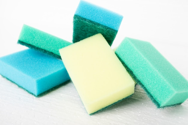 Cleaning after repair, facade cleaning. colorful sponges on a white background
