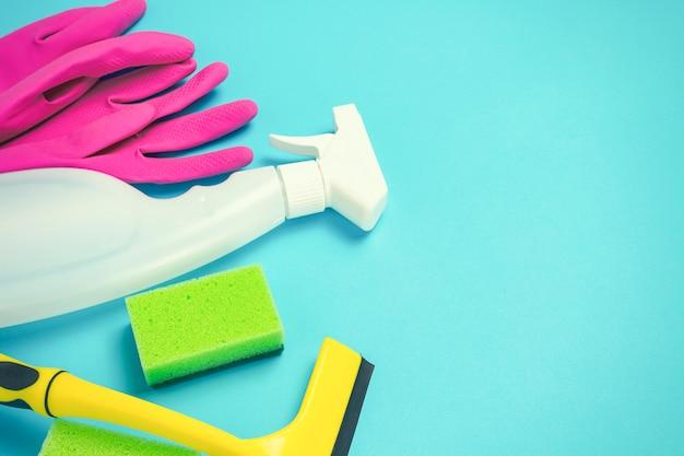Чистящие и чистящие принадлежности, перчатки, спрей, губки, скребок для окон на синем фоне. концепция уборки. плоская планировка, вид сверху