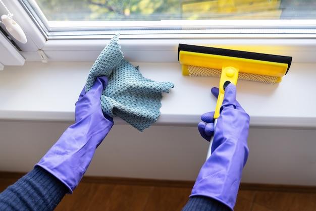 Очистка и концепция очистки. молодая девушка в фиолетовых перчатках держит тряпку и швабру для мытья окон.