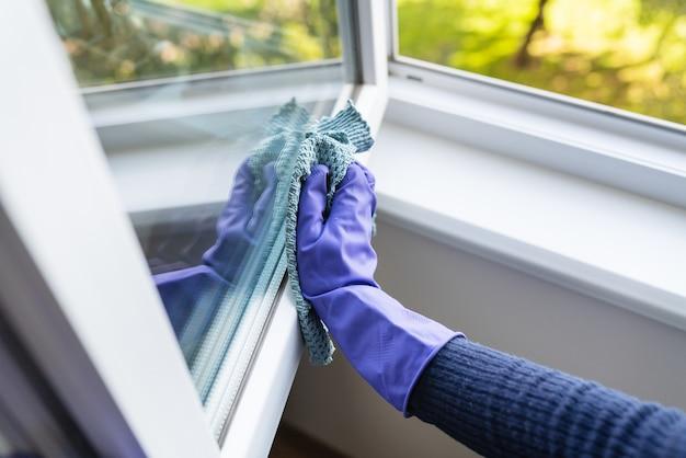Очистка и концепция очистки. молодая девушка в фиолетовых перчатках вытирает тряпкой пыль на подоконнике и окне.