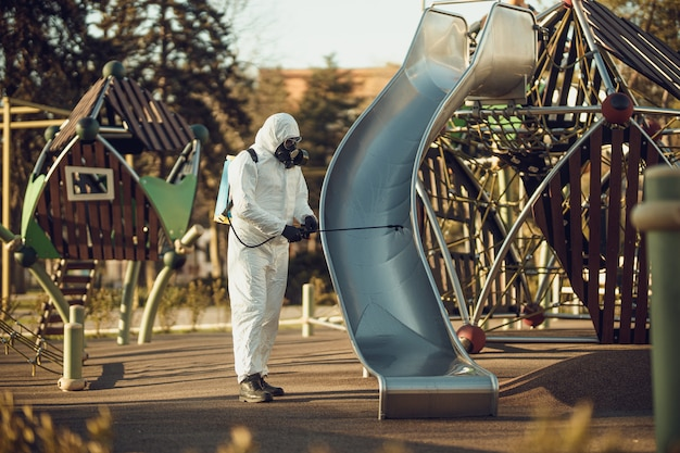 Чистка и дезинфекция на детской площадке в комплексе города на фоне эпидемии коронавируса.