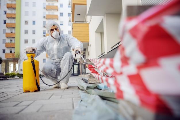 Уборка и дезинфекция снаружи вокруг зданий, эпидемия covid-19. сессионные бригады по дезинфекции. профилактика инфекций и борьба с эпидемиями. е костюм и маска.