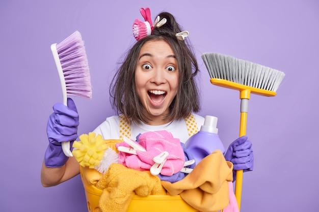 Pulizia appartamento. la casalinga emotiva felice con la spazzola e le mollette da bucato nei capelli tiene le forniture per portare la casa in ordine pone vicino al cesto della biancheria isolato su sfondo viola. doveri domestici