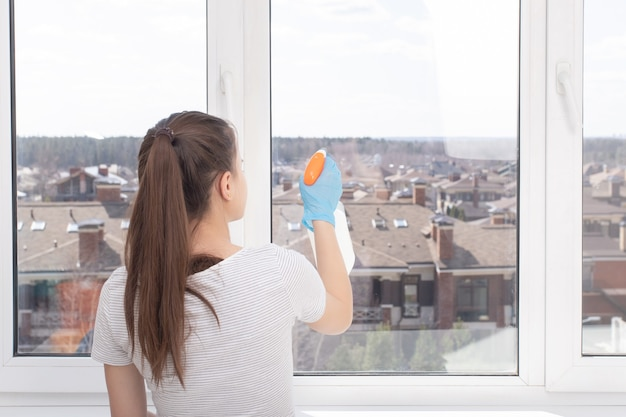 Cleaning of apartments, offices, cottages, warehouses, garages. young woman washes a window with a cleaning spray