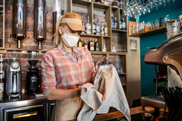 Cleaning the bar in the restaurant. an adult blonde woman in a waiter's uniform stands behind the bar and wipes freshly washed wine glasses with a beige cloth. restaurant work and corona virus