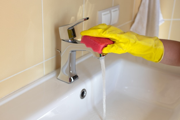 Cleaning bathroom sink and faucet with detergent in yellow rubber gloves and pink sponge.