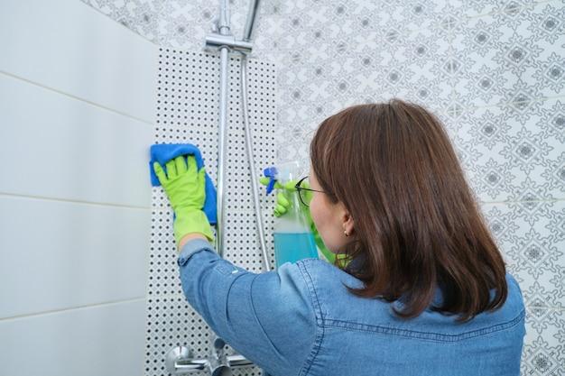 バスルームの掃除、ぼろきれと洗剤の手袋をした女性、シャワーの洗濯と磨き、ガラス、蛇口、タイル張りの壁