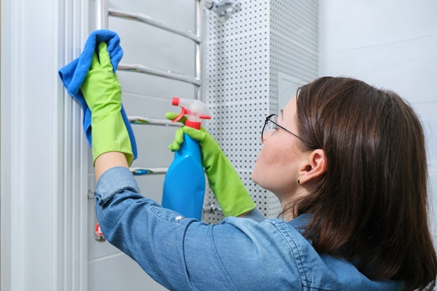 Cleaning bathroom, woman polishing heated towel rail