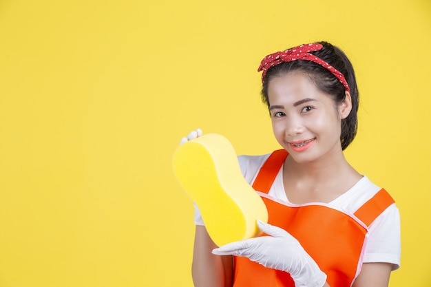 Cleaning . a beautiful woman with a cleaning device on a yellow .