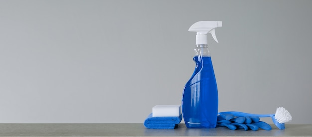Cleaning blue spray bottle with plastic dispenser, scrubbing brush