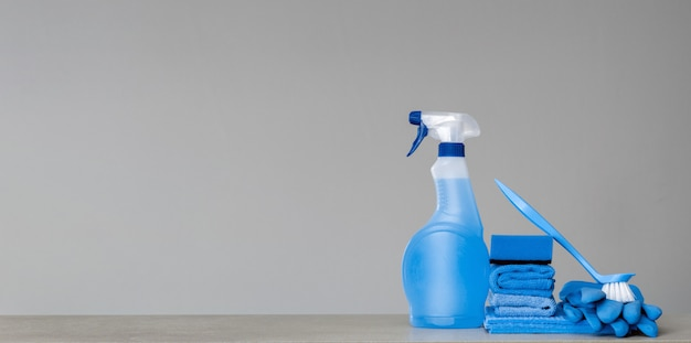 Cleaning blue spray bottle with plastic dispenser, sponge, scrubbing brush for dish, cloth for dust and rubber gloves on grey