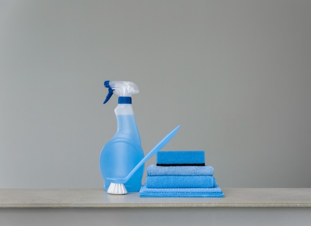 Cleaning blue spray bottle with plastic dispenser, sponge, scrubbing brush for dish