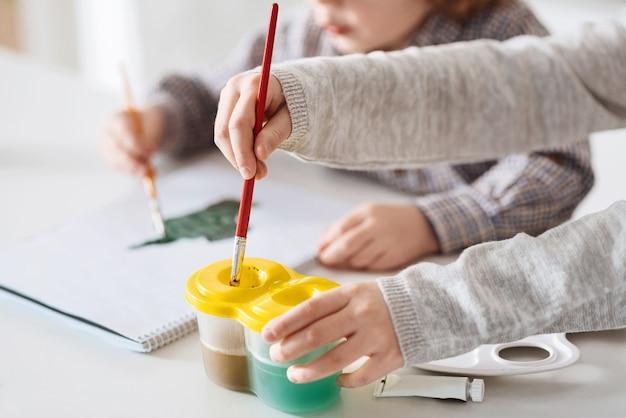 청소용 브러시. 흰색 테이블에 앉아 함께 시간을 보내는 동안 기이 한 그림을 그리기 위해 수채화를 사용하는 예술적 열심히 일하는 호기심 많은 형제