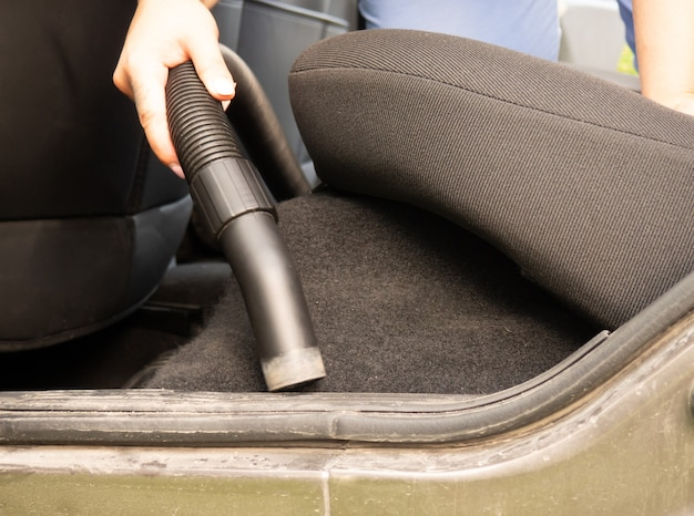 Cleaning the car, the girl collects the crumbs with a vacuum cleaner in the car