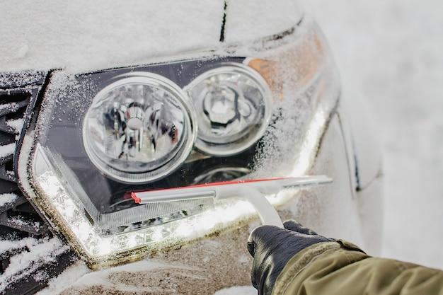 겨울 날에 자동차 조명을 청소합니다. 추운 날씨에 눈이 덮여 차. 겨울 여행을 위해 차를 준비하십시오.