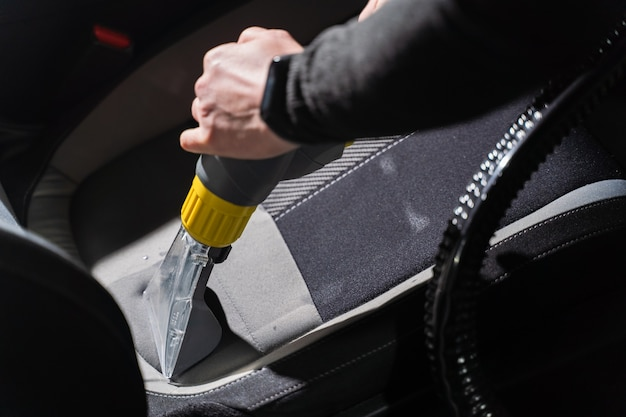 Cleaning car salon dry cleaning with vacuum cleaner. professional use of a steam vacuum cleaner to remove stains