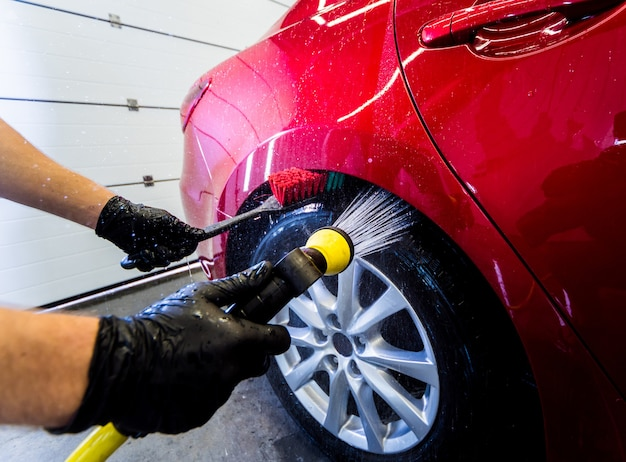 Cleaning the car wheel with a brush and water