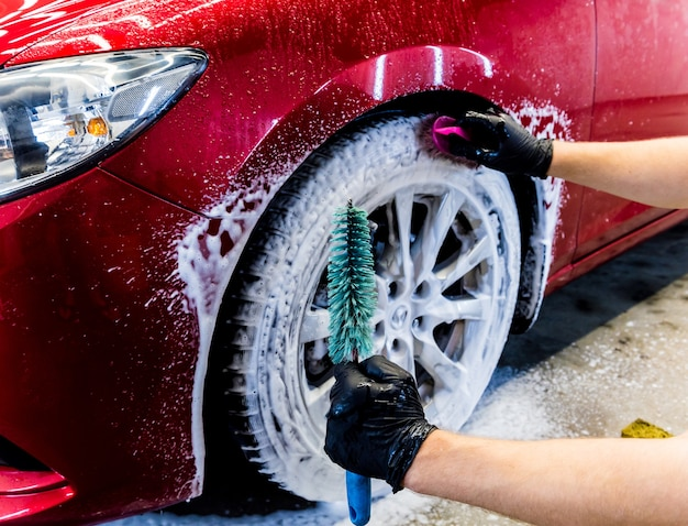 Cleaning the car wheel with a brush and water.