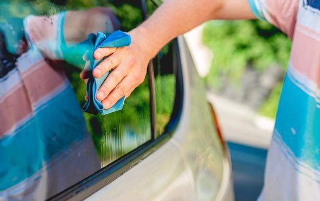 マイクロファイバー布で車の窓を掃除する