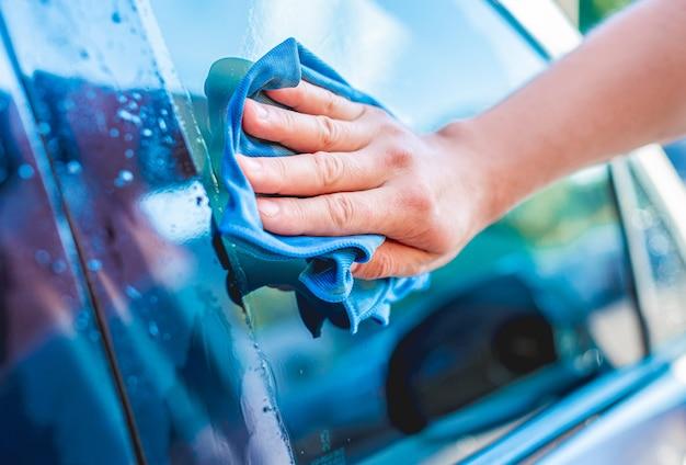 マイクロファイバーのぼろきれで車の窓を掃除する