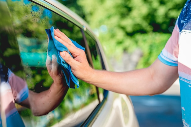 Cleaning car window with microfiber rag