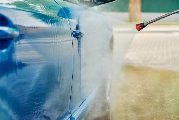 Cleaning car with high pressure water at car wash station