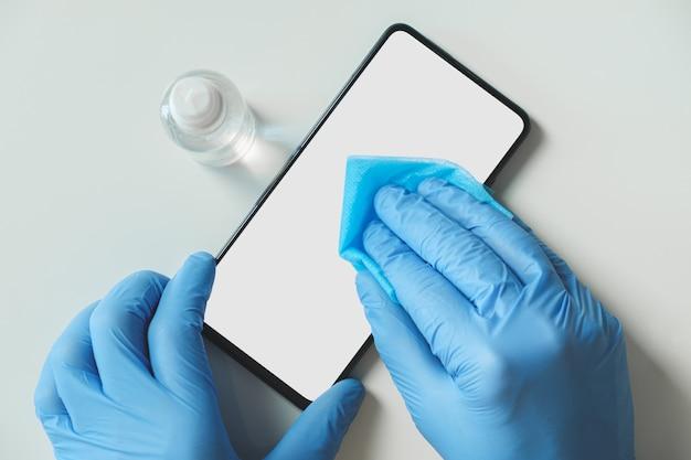 携帯電話を消毒剤と布で洗浄します。個人衛生の概念、ウイルスからの保護、covid-19普及啓発
