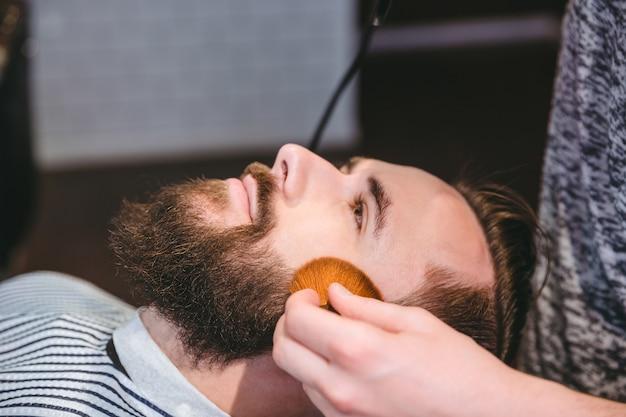 理髪店で柔らかいブラシで散髪した後、クライアントの顔を掃除する