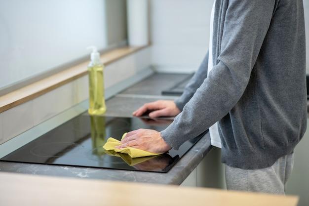クリーニング。キッチンのテーブルの表面を掃除している男性の写真をクローズアップ