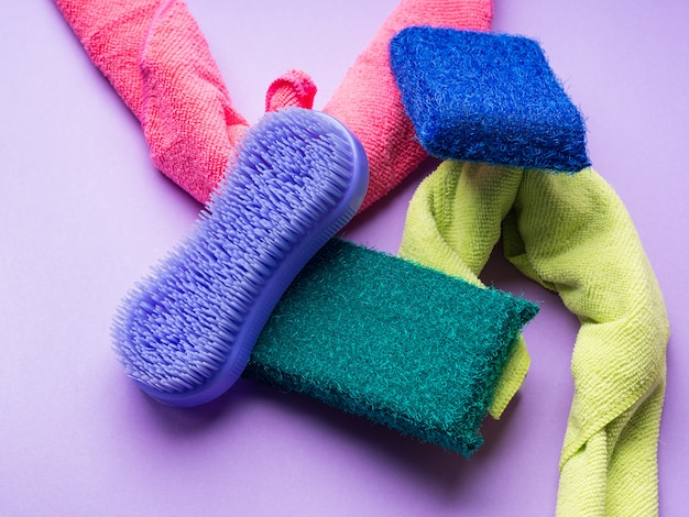 Чистящие салфетки и губки на цветном фоне