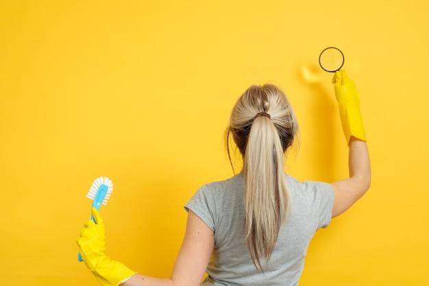 清掃会社。プロのホームオフィスのクリーンアップ。拡大鏡と黄色のブラシとゴム手袋の女性。