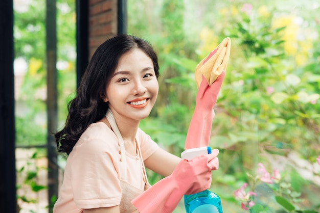 Cleaning concept. cheerful asian woman cleaning window.